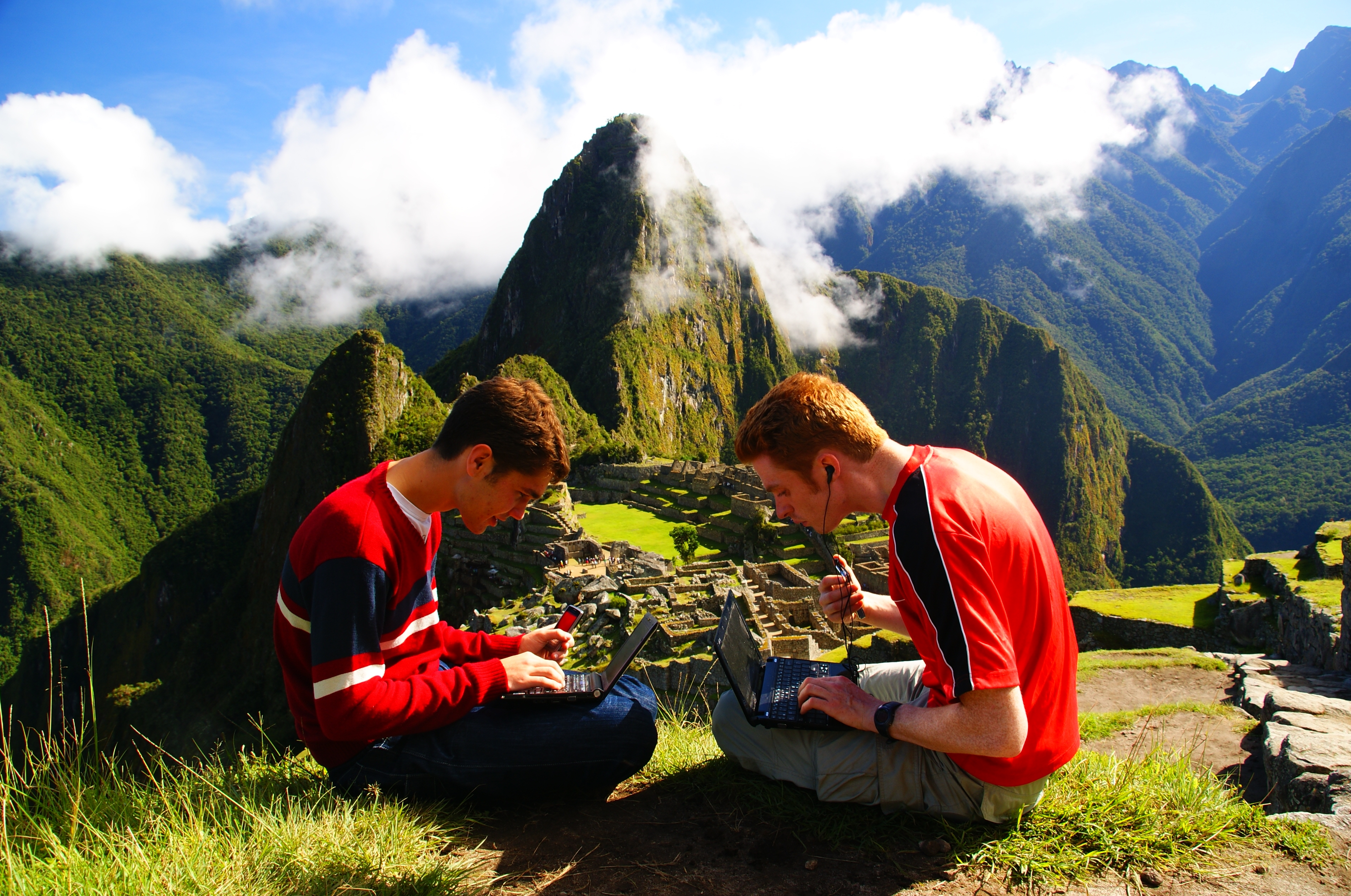 Nomadic Samuel travel blogging on top of Machu Picchu