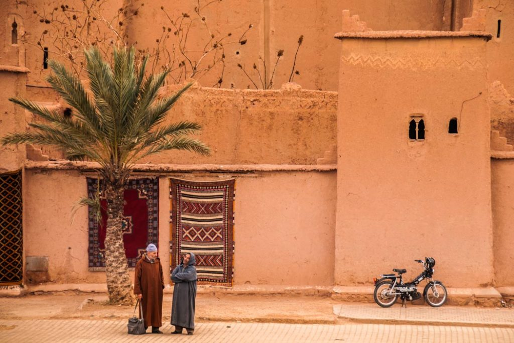 This couple chatting in Ouarzazate, Morocco, is a beautiful symbol of two quintessential images of the Sahara desert that stretches behind the city.