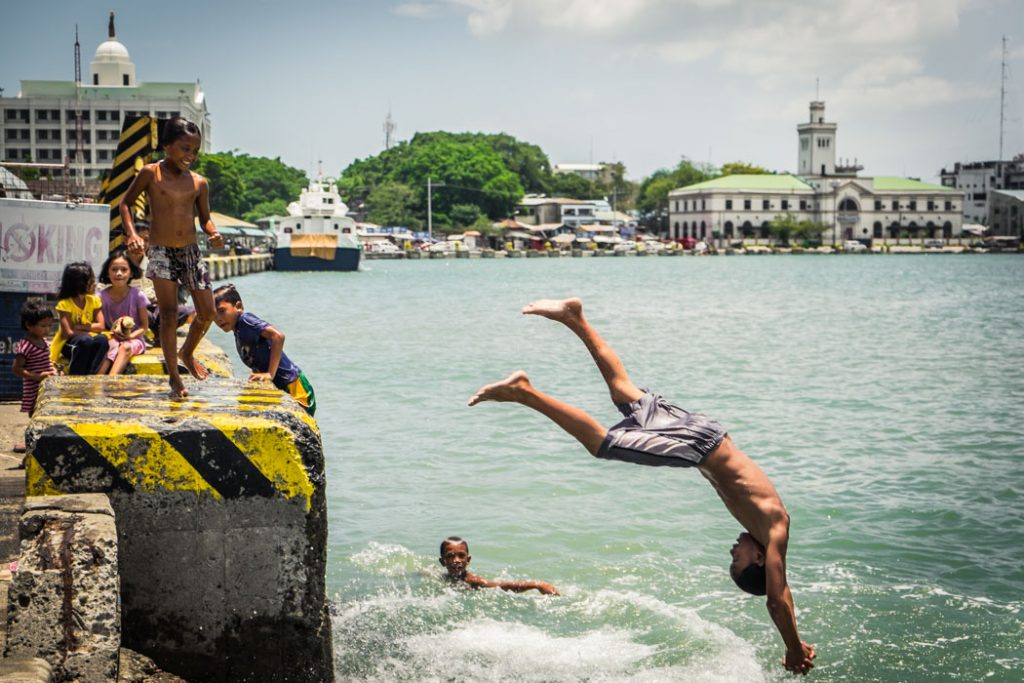 Filipino kids don't need too much to have fun. These are jolly children at the port in Iloilo, Philippines on a hot sunny day.