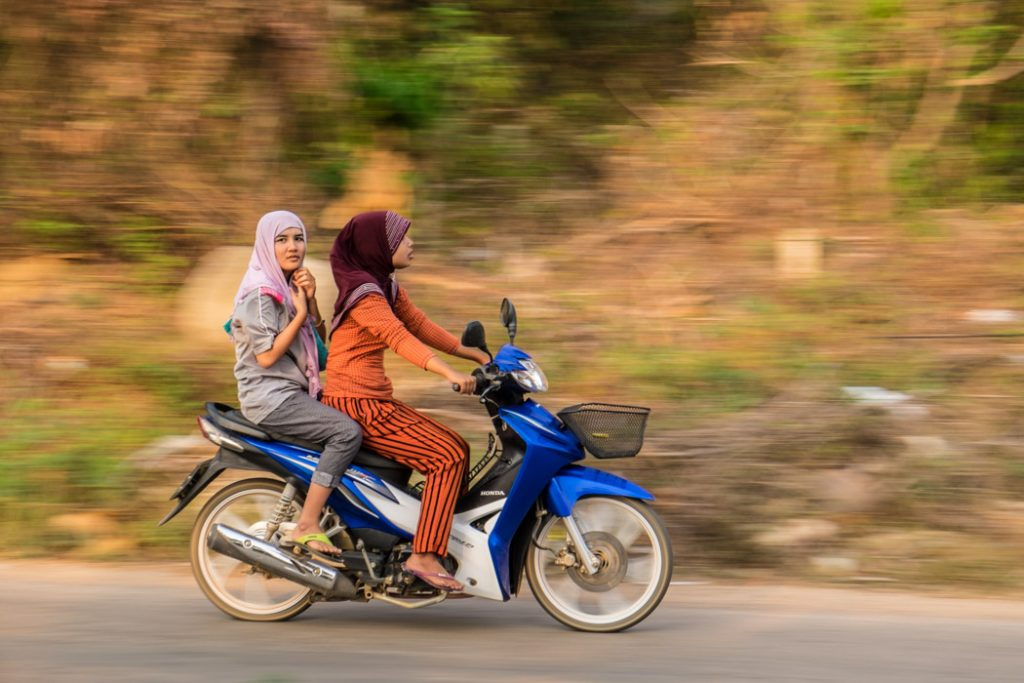 When the eye of a camera meets human eyes. Two young girls riding a scooter in the almost deserted southern tip of Koh Lanta, Thailand.