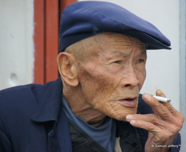 Distinct local Chinese man with a beret smoking in Dali, China