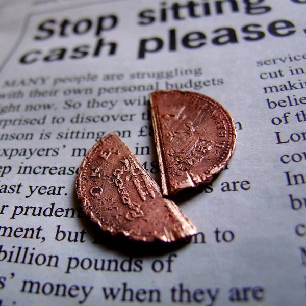 broken penny on newspaper split in half