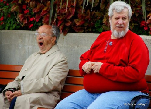 Yawning man sitting down on a park bench in Chicago candid portrait