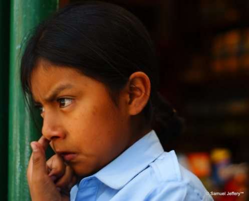 Young girl picking her nose on the streets of Quito, Ecuador candid portrait