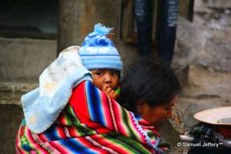 Baby on back of mother in markets of La Paz, Bolivia