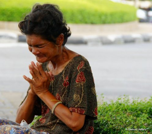Thai lady praying and begging for money in Bangkok, Thailand candid portrait