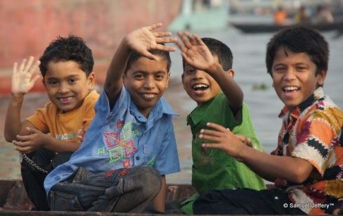 Smiling and waving boys on a simple boat in Dhaka, Bangladesh